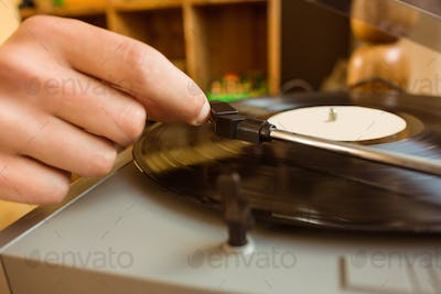 Young man putting on a vinyl at home in the living room