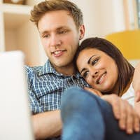 Happy young couple relaxing on the couch with laptop at home in the living room