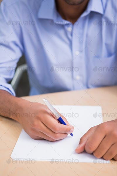 Close up mid section of businessman writing document at office desk
