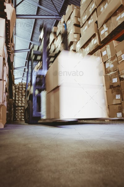 Forklift amid rows of shelves with boxes in large warehouse