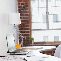 Laptop on desk with glasses and notepad in the office