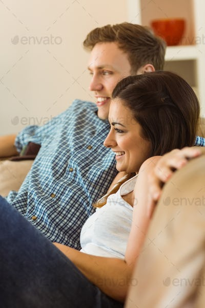 Happy young couple relaxing on the couch at home in the living room
