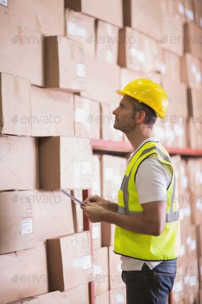 Warehoue worker using digital tablet in warehouse