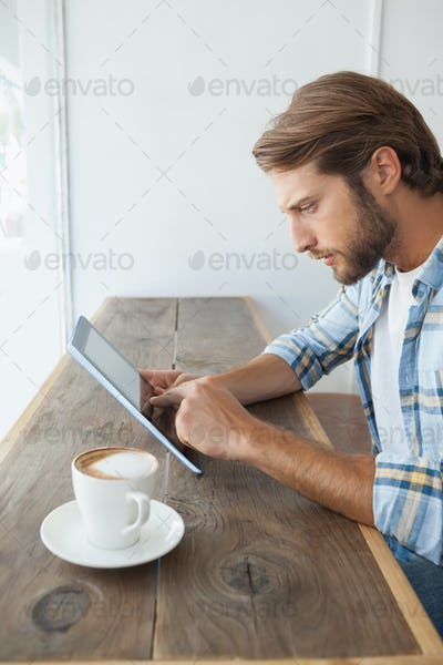 Casual man having a coffee using tablet at the coffee shop