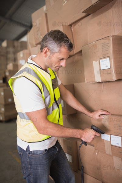 Side view of manual worker scanning package in the warehouse