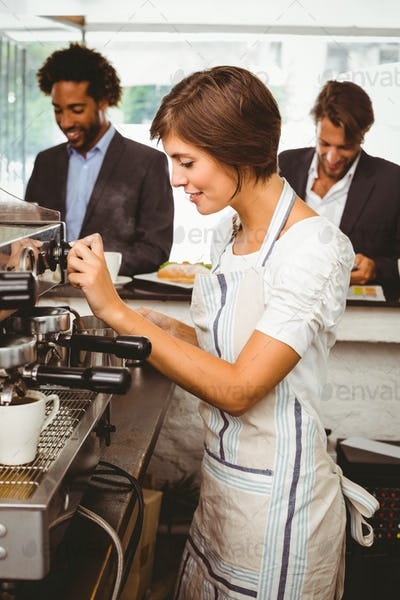 Pretty barista making cup of coffee at the coffee shop