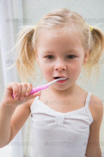 Cute girl brushing her teeth at home in the bathroom