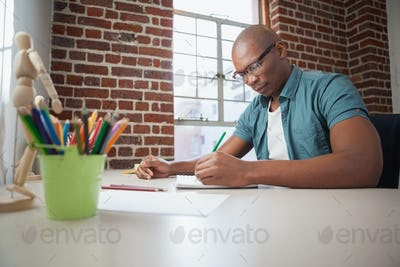 Designer sketching on paper with pencil in the office