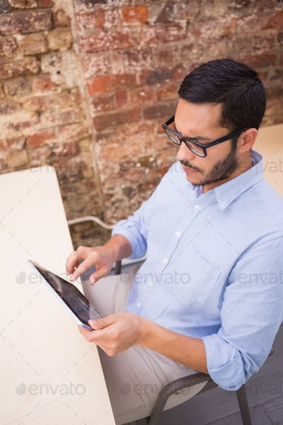 Side view of businessman using digital tablet at office desk