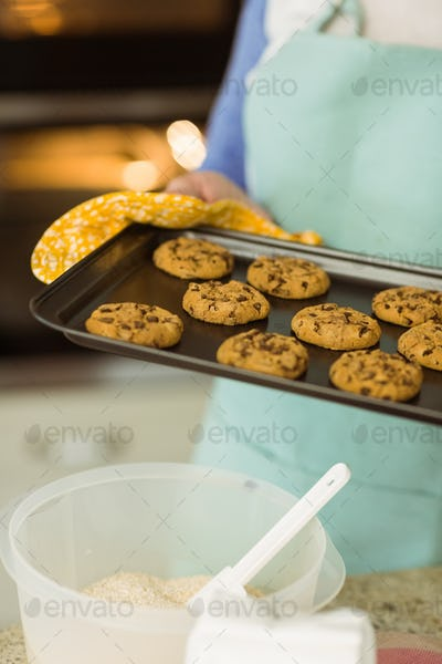 Woman showing tray of fresh cookies at home in the kitchen