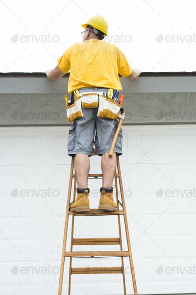Contractor standing on ladder