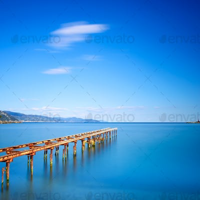 Wooden pier or jetty remains on a blue ocean lake. Long Exposure