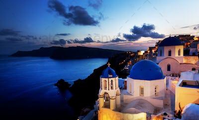 Oia town on Santorini island, Greece at night. Rocks on Aegean sea.