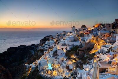 Oia town on Santorini island, Greece at sunset. Famous windmills