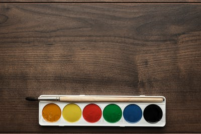 Box Of Paints And A Brush On The Table