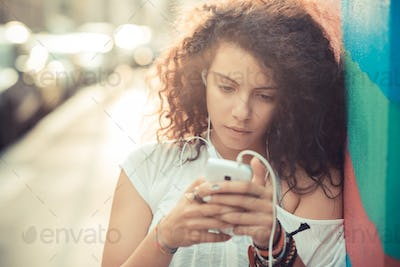 young beautiful moroccan curly woman using smartphone