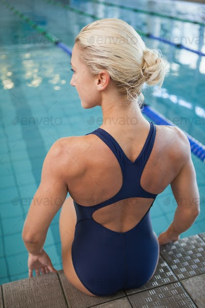 Rear view of a fit female swimmer sitting by the pool at leisure center