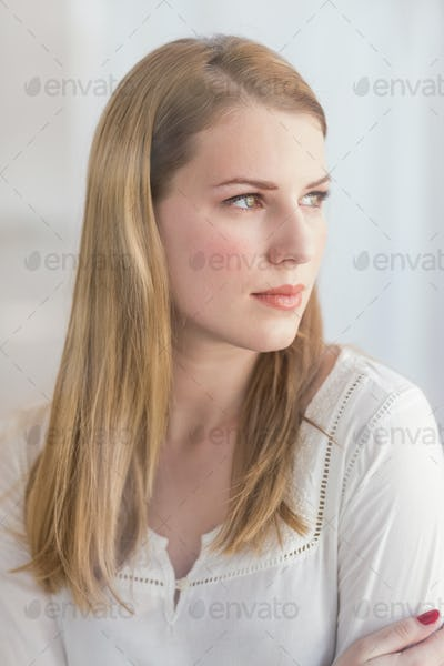 Portrait of a blonde woman looking away at home in the living room