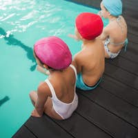 Cute swimming class sitting poolside at the leisure center