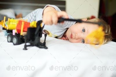 Little blond boy playing with car.