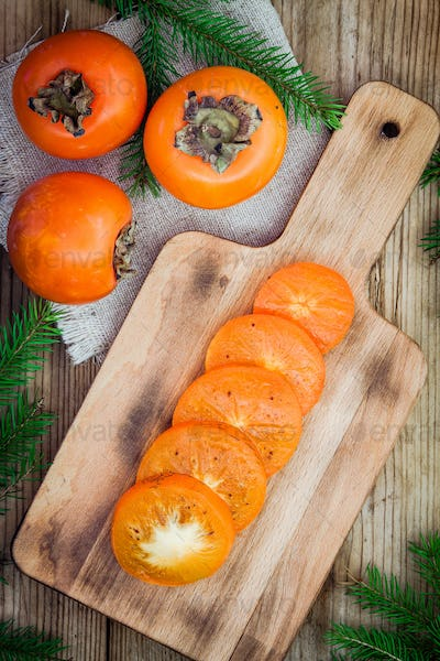 Fresh organic persimmon with slices on wooden board