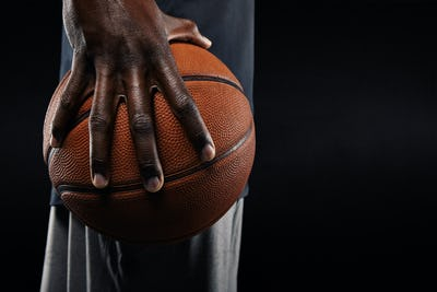 Hand of basketball player holding a ball