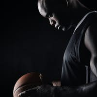 African sportsman holding basketball