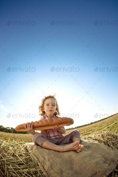 Child with bread sitting on hayrick