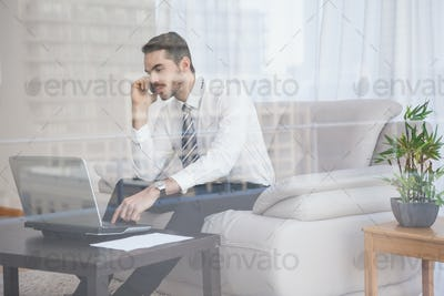 Businessman working on his couch seen through glass at home in the living room