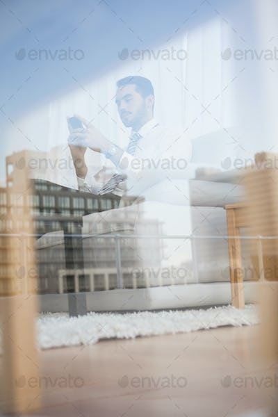 Businessman texting on his couch seen through glass at home in the living room