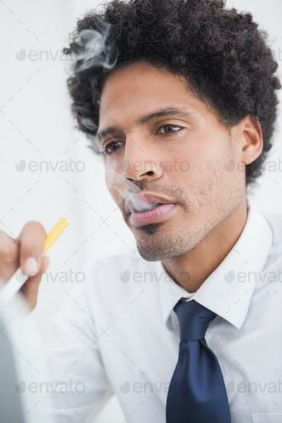 Portrait of a businessman smoking in his office