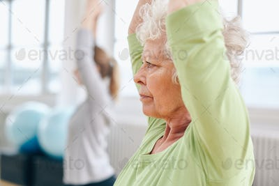 Senior woman practicing yoga at gym