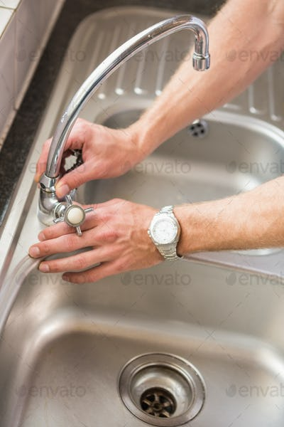 Man fixing tap with pliers at home in the kitchen