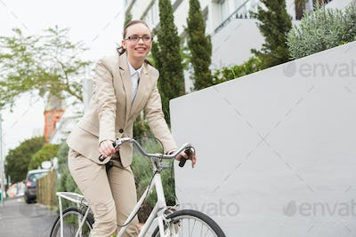Young businesswoman riding her bike outside in the city