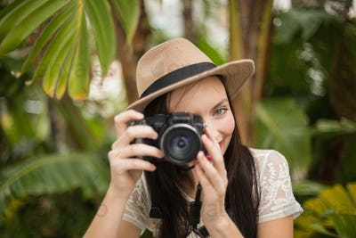 Pretty brunette taking a photo outside in the garden