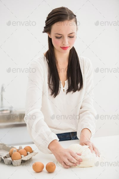 Pretty brunette making dough on counter at home in the living room