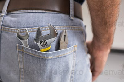 Handyman with tools in back pocket in the kitchen