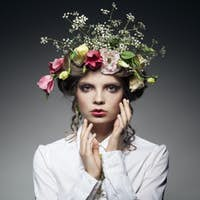 portrait of beautiful young woman with flowers in hair isolated on dark background with copyspace