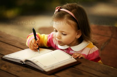 a little girl learning to write