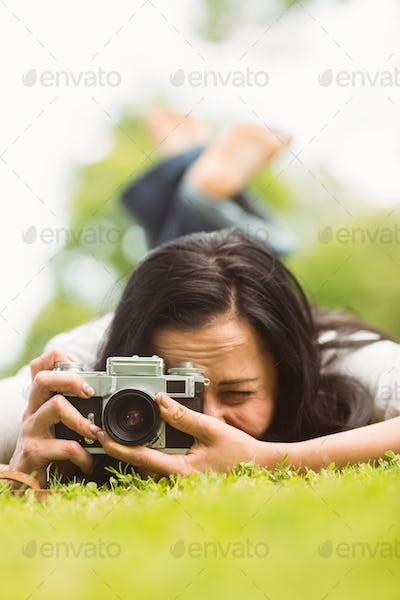 Brunette lying on grass with retro camera taking picture in the park