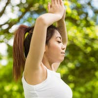 Side view of healthy and beautiful young woman with joined hands over head at park