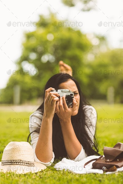 Brunette lying on grass taking photo in the park