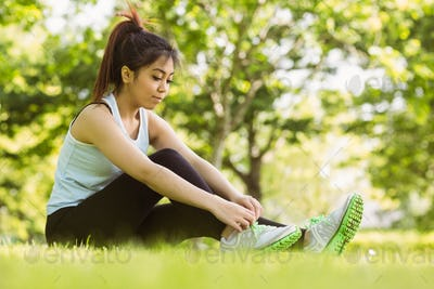 Full length of healthy young woman relaxing in park as she ties shoelace