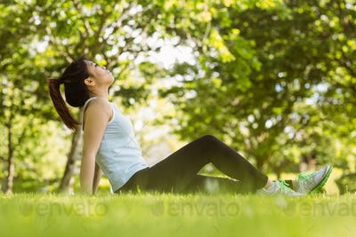 Side view of healthy young woman sitting on grass in park