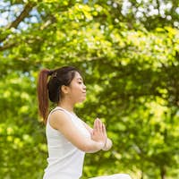 Full length of healthy and beautiful young woman sitting with joined hands at park
