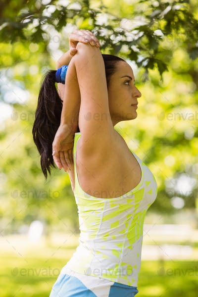 Focused fit brunette stretching in the park on a sunny day