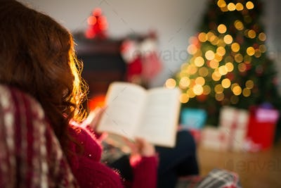 Rear view of redhead reading at christmas at home in the living room