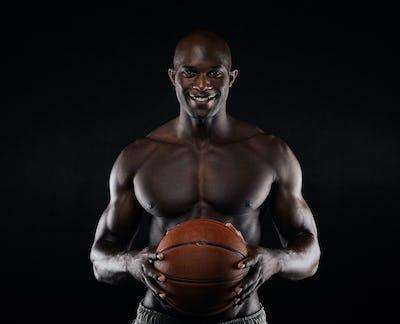 Shirtless basketball player looking at camera smiling.