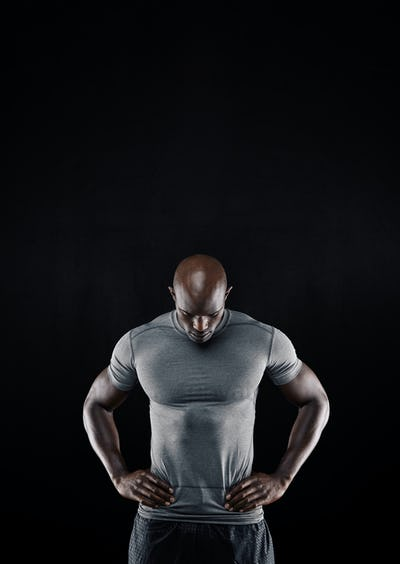 Muscular young man looking down