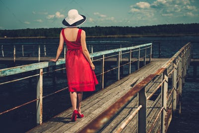 Stylish woman in white hat and red dress standing on old wooden pier